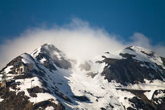 Snowy mountain peak staring out the clouds in blue sky in sunlight, pyrenees, south france Royalty Free Stock Images