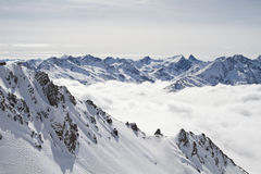 Snowy mountain peaks above the clouds Royalty Free Stock Photos