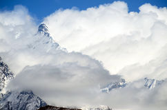 Snowy mountain peaks barely visible through clouds Royalty Free Stock Photo