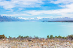 Snowy mountain peaks over a blue lake Stock Images