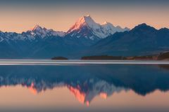 Snowy mountain range reflected in the still water of Lake Pukaki, Mount Cook, South Island, New Zealand. The turquoise water. royalty free stock photos