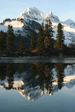 Snowy mountain reflection. Scenic view of snow capped mountain and trees reflected on lake royalty free stock photos