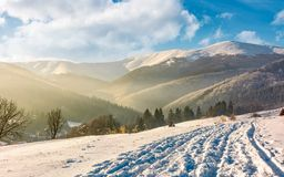 Snowy mountain ridge above the rural area. Lovely countryside winter scenery Stock Image