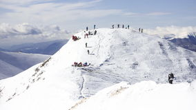 Snowy Mountain ridge with groups of people on top. The ridge of a mountain with snow on it against a cloudy blue sky. Many people preparing to ski or to ride the stock images