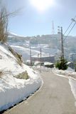 Snowy Mountain Road. Picture of a winding mountain road leading to a small village on a sunny day in the middle of winter Royalty Free Stock Photography