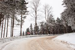 Snowy mountain road. Risk of ice. Path in snowy woods. Royalty Free Stock Photo