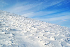 Snowy mountain slope and blue sky Stock Photography
