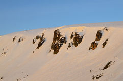 Snowy mountain slope on sunrise Stock Photo