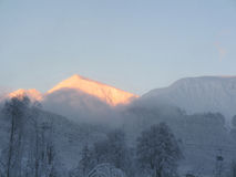 Snowy mountain top at sunset royalty free stock image