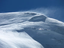 Snowy mountain top in the wind. The snow covered mountain top of the Allalinhorn (4027) near Saas-Fee Switzerland stock image