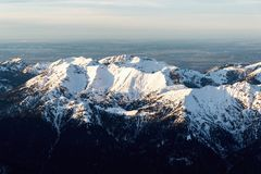 Snowy mountain tops in sunset. Aerial view of a group of snowy mountain tops in front of a green landscape till horizon Royalty Free Stock Photo