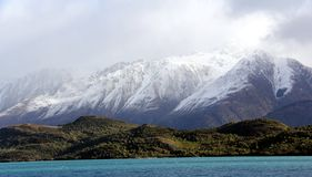 Snowy Mountain towering over lake wanaka New Zealand.  Royalty Free Stock Images