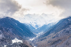 Snowy mountain valley under cloudy skies Royalty Free Stock Photo