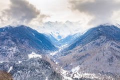 Snowy mountain valley under cloudy skies Royalty Free Stock Image