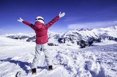 Snowy mountain view. Young happy woman snowboarder standing on the top of the mountain rising arms to the sky. North Alps, France stock images