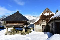 Snowy mountain village with ancient palloza houses made with stone and straw and galician granary horreo. Piornedo, Lugo, Spain. stock photos
