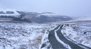 Snowy mountains. A snowy scene in the wicklow national park.A road disappears into the distance tywords snow covered mountains Royalty Free Stock Image