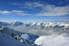 Snowy Mountains. Austrian Alps, snow-capped mountains, clouds below royalty free stock photos