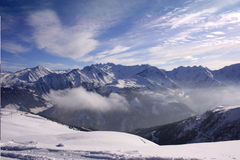 Snowy Mountains. Austrian Alps, snow-capped mountains, clouds below royalty free stock image