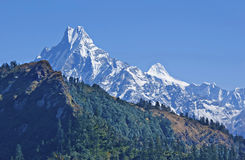 Snowy mountains. Jagged snow-capped peak Machapuchare and mountains with a forest on the background of blue sky Royalty Free Stock Photos