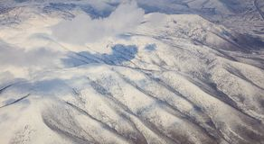 Snowy mountains background and white clouds above them. Aerial photo from plane window. Stock Photography