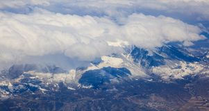 Snowy mountains background and white clouds above them. Aerial photo from plane`s window. Stock Images