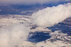 Snowy mountains background and white clouds above them. Aerial photo from plane`s window. Royalty Free Stock Photo