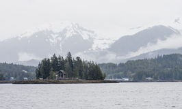Snowy Mountains Behind Cabin on Island Royalty Free Stock Photography