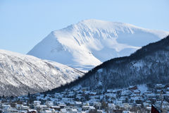 Snowy mountains on a bright Sunny day with houses at the bottom. Snowy mountains on a bright Sunny day Royalty Free Stock Photography