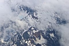 Snowy mountains. Through the clouds (photo taken from airplane Stock Image