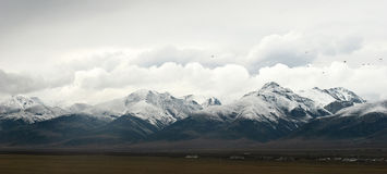 Snowy mountains in clouds in Tibet panorama view Royalty Free Stock Photo