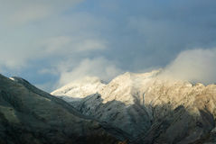 Snowy mountains in clouds in Tibet panorama view Royalty Free Stock Images