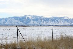 Snowy mountains and fence. Blue, snow-covered mountains, a snowy field, and a fence Royalty Free Stock Photography
