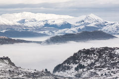 Snowy mountains with fog Stock Photos