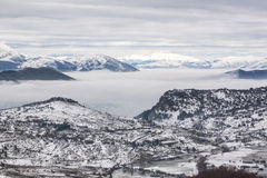 Snowy mountains with fog Stock Photography