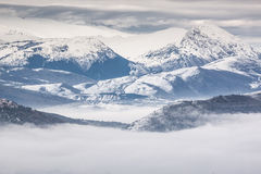 Snowy mountains with fog Stock Images