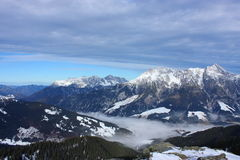 Snowy mountains. With a foggy valley and a blue but cloudy sky Royalty Free Stock Images