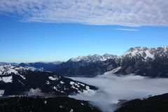 Snowy mountains. And a foggy valley under a blue sky Royalty Free Stock Photos