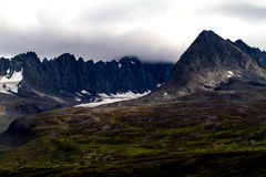 Snowy Mountains and Green Valley Alaska. Under cloudy skies, a jagged Alaskan mountain range with patches of snow reaches upward. Beneath the snow line is a rich Royalty Free Stock Photography