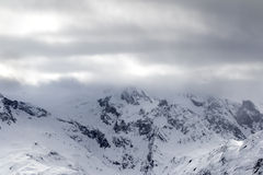 Snowy mountains in haze and storm clouds Stock Image