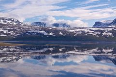 Snowy mountains by lake. Norwegian landscape in early summer mirroring on surface of a lake Royalty Free Stock Photos