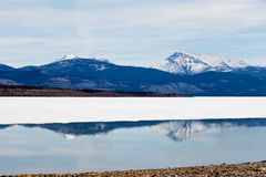Snowy Mountains mirrored on Lake Laberge, Yukon Royalty Free Stock Images
