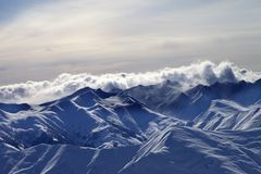 Snowy mountains in mist at winter evening Stock Photos