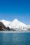 Snowy mountains by ocean Royalty Free Stock Photos