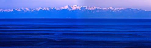 Snowy mountains over blue wintery sea Stock Photos