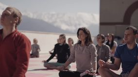 Snowy mountains. People do yoga at outdoor playground in sunny morning, beating in chest. Positions. Concentration stock video