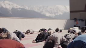 Snowy mountains. People do yoga at outdoor playground in sunny morning, stretching. Fresh air. Concentration stock video