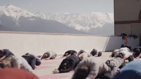 Snowy mountains. People do yoga at outdoor playground in sunny morning, stretching. Meditation. Concentration stock video footage