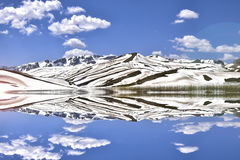 Snowy mountains reflecting on lake Stock Photos