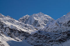 Snowy mountains. Snow covered mountains under the sky Royalty Free Stock Image